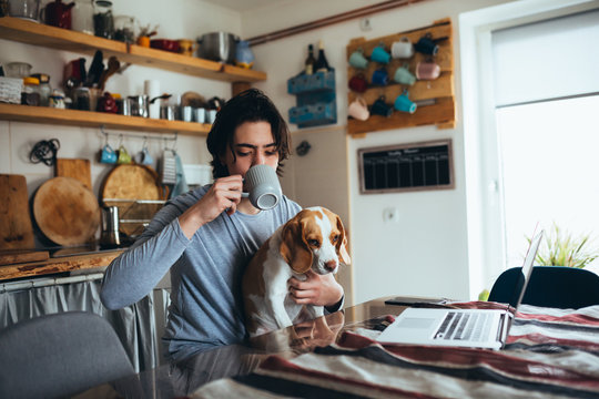 young man with his dog in kitchen at home, morning scene,