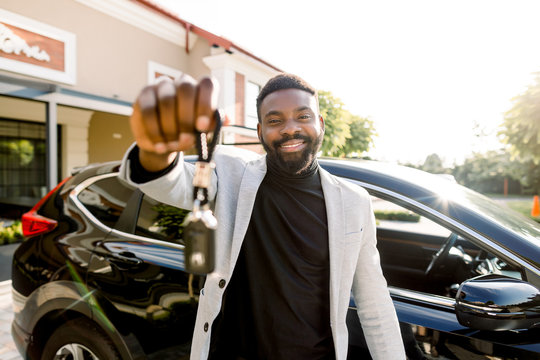 Portrait of African man car seller holding car keys. Attractive cheerful young African man smiling showing car keys to his new auto posing outdoors at the dealership salon
