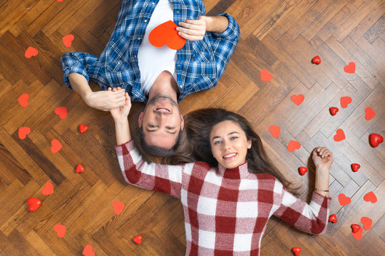 Top view of romantic couple lying on floor, expressing love to soul mate