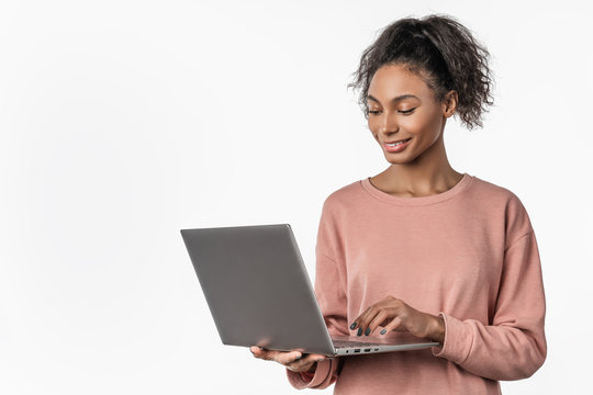 Smiling woman in casual clothes holding laptop and sending email standing over white background