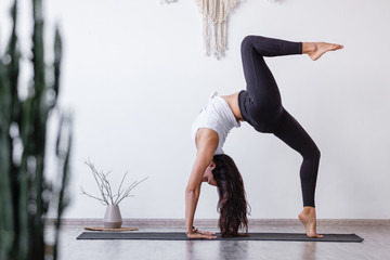 Young woman asian yoga lover doing standing in Bridge exercise, One legged Wheel pose on floor in cozy white room. Working out, wearing sportswear, black pants, bra, indoor full length, home interior