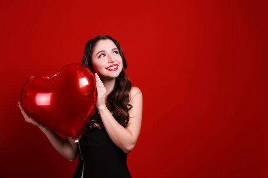 Portrait of young brunette woman posing with helium inflated air balloon. Happy valentine's day concept. Joyful female with wavy hair over colorful background. Close up, copy space for text.