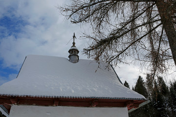 snow-covered roof of the chapel in the mountains
