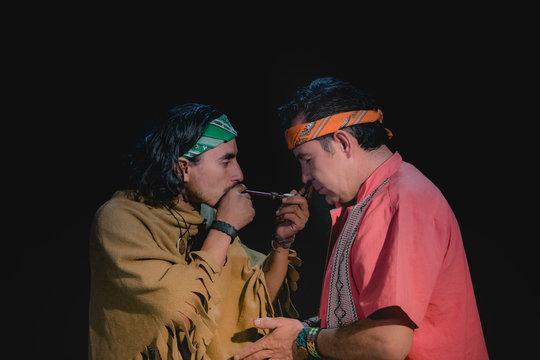 shaman or sorcerer men giving sangha medicine, ayahuasca, during prehispanic ritual on black background