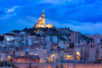 Fototapete - Panoramic view of night Old Port and the Basilica of Notre Dame de la Garde on the background, on the hill, Marseille, France