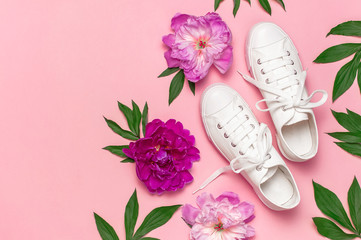 White female fashion sneakers and pink purple flowers peonies on pink background. Flat lay top view copy space. Women's shoes. Stylish white sneakers. Fashion blog or magazine. Spring shoe concept Wall mural