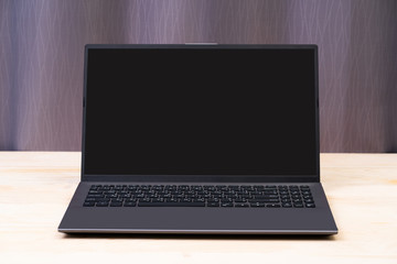 Blank black screen laptop computer on wood table