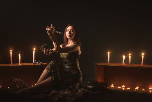 a witch with a snake on her neck and in her hands sits in a haze against a background of candles and a skeleton