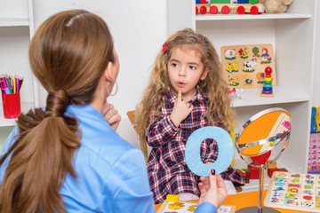 Young girl  in speech therapy office. Preschooler exercising correct pronunciation with speech...