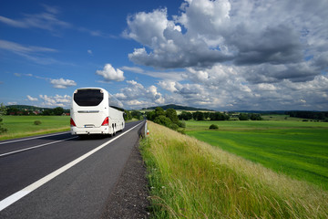 White bus driving on the asphalt road in a rural landscape