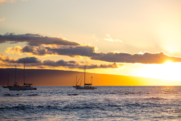 sail boats on the ocean at sunset