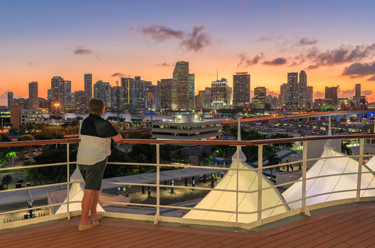Woman on a cruise ship overlooking the Miami skyline after sunset