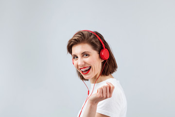 Lovely woman in red earphones listening to music