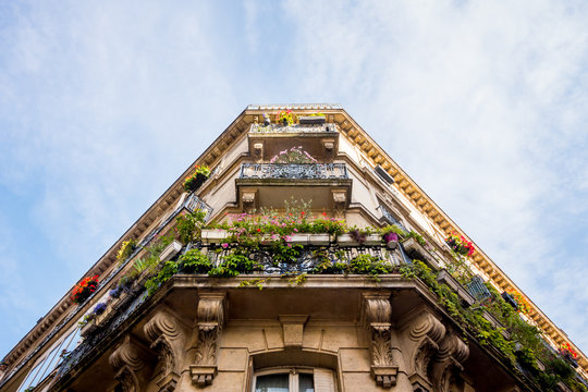 Looking up at corner apartments with balconies filled with flowers in Paris, France.
