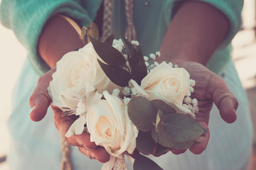 Vintage cold blue colors image of woman hands taking a group of white romantic roses - concept of decorations and wedding bouquet - people and romance