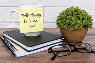 Inspirational quotes - Hello Monday, let's do this text on sticky note on top of table