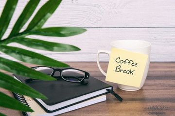 Coffee break text on sticky note on top of table
