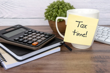 Tax time text written on sticky note with calculator on top of desk - business and financial concept