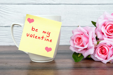 Be my valentine text on a sticky note with pink roses and cup of coffee