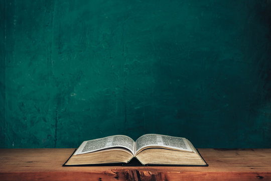 Open bible on a red old wooden table. Beautiful green wall background.