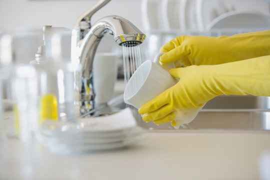 Woman with rubber gloves rinsing coffee mug in sink.