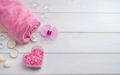 Türaufkleber Spa Spa treatments as a gift for Valentine's Day. Pink towel with a flower, shells and pink sea salt in the form of a heart on a white wooden background. Beauty salon