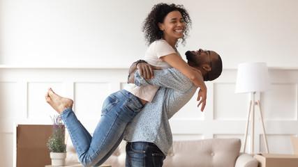 Successful black man raising up happy smiling wife.