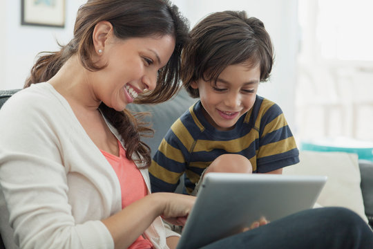 mother and son playing on pc tablet together