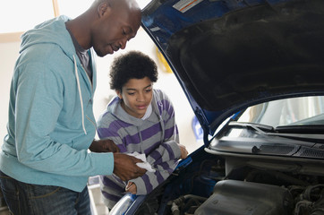 father teaching son about car repair