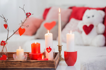 Burning candles on white table in interior. Valentines day conce