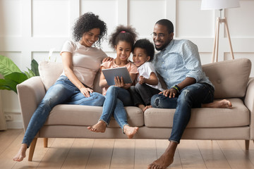 Happy african american family using tablet together. Fotomurales