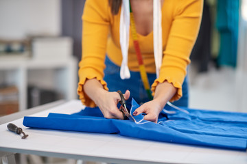 Dedicated seamstress standing next to table and cutting textiles for elegant dress.