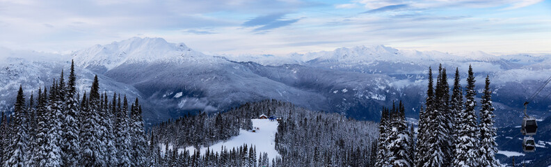 Whistler, British Columbia, Canada. Beautiful Panoramic View of the Canadian Snow Covered Mountain Landscape during a cloudy and colorful winter sunset.