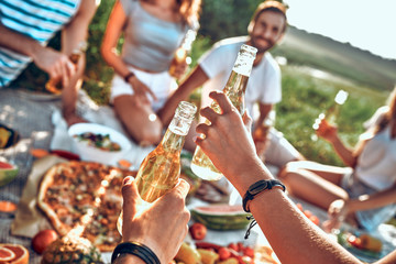 Group of young people eating and drink beers during picnic on park
