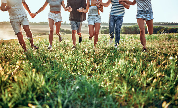 Group of friends running on grass meadow on country side.
