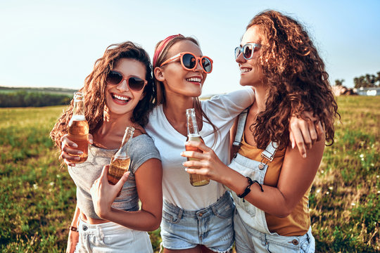 Candid of young attractive three girl group of friends cheers holding a bottle beer drinking for celebration party in evening sunset