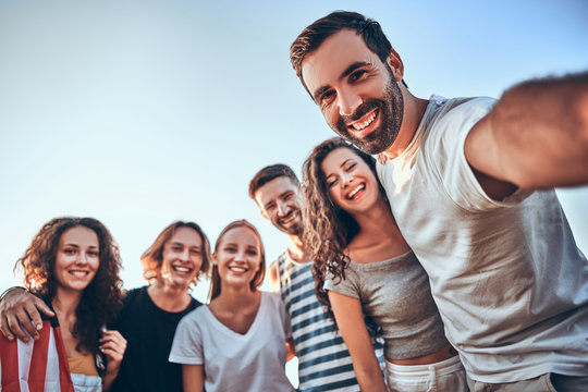Group of happy teenage friends taking selfie on nature. Young woman with american flag background.