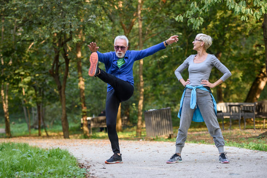 Cheerful active senior couple exercising in the park together. Exercise to stop aging.