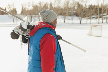 Man walking with hockey stick and skates outdoors