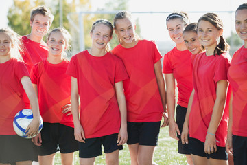 Girls soccer team smiling in red jerseys.