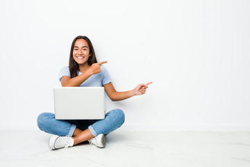 Young mixed race indian woman sitting working on laptop excited pointing with forefingers away. Fotomurales