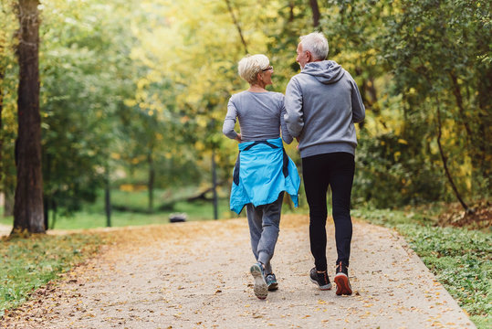 Cheerful active senior couple jogging in the park. Exercise together to stop aging.