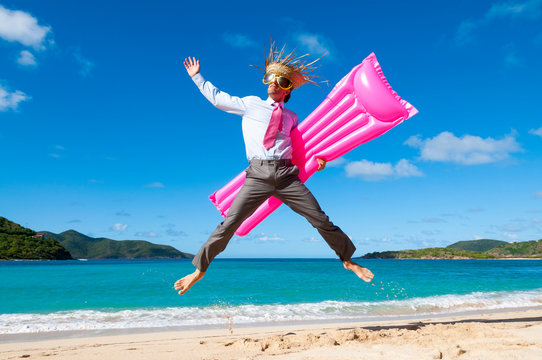 Happy businessman wearing straw hat and oversized sunglasses jumping for joy with a pink lilo on a tropical beach
