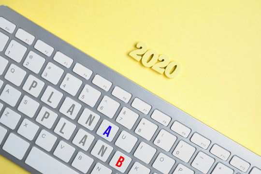 Wooden figures 2020 with a keyboard with the inscription Plan A and Plan B on a yellow background.