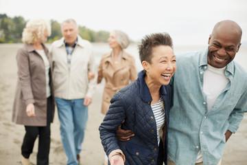 Mature friends walking along the beach