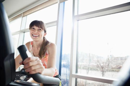 Woman exercising on stationary bike in fitness center
