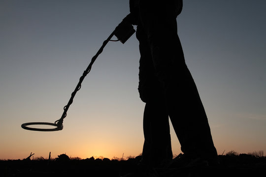 Silhouette of a man with a mine detector on the background of the setting sun