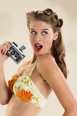 Surprised pin-up girl holding vintage camera