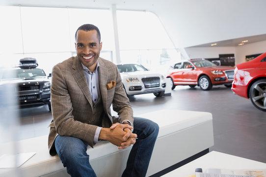Portrait of smiling man in car dealership showroom