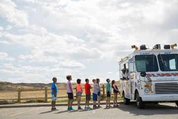 Group of children queuing for ice cream on road